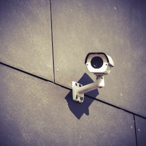 Security camera on gray office building wall