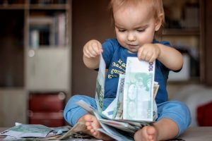Inspired toddler boy holds hundred Euro denominations