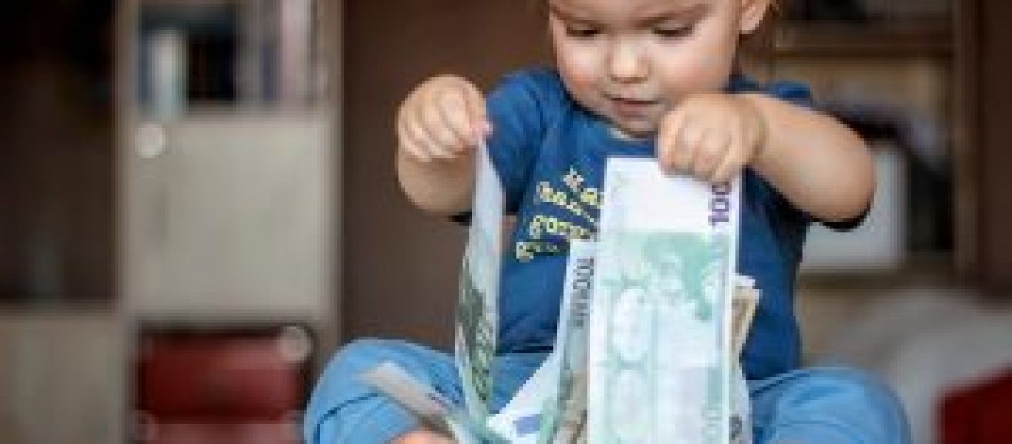 Inspired toddler boy holds hundred Euro denominations